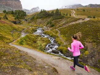 A woman trail running in the mountains.