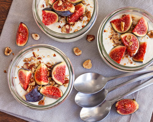 Yogurt deliciously served in jars topped with fresh figs and roasted hazelnuts